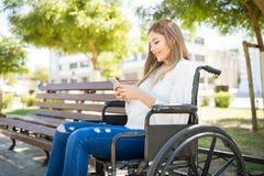 Mulher na cadeira de rodas com um smartphone Fotografia de Stock