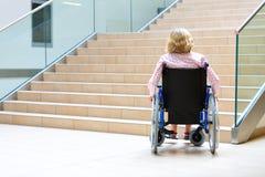 Mulher na cadeira de rodas e nas escadas Imagem de Stock