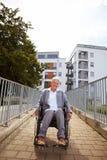 Mulher na cadeira de rodas na parte dianteira Fotografia de Stock Royalty Free