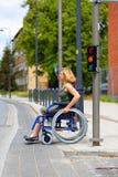 Mulher na cadeira de rodas que cruza a rua Foto de Stock Royalty Free