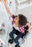 Mulher na cadeira de rodas que esforça-se para alcançar algo da prateleira imagens de stock royalty free