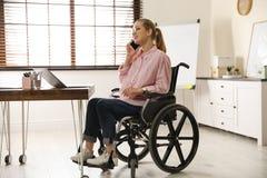Mulher na cadeira de rodas que fala no telefone na tabela fotos de stock