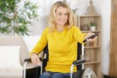 Mulher na cadeira de rodas que olha cozinhando o programa imagem de stock royalty free