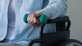 Mulher na cadeira de rodas que tenta desenvolver seu braço após o curso, levantando o peso filme