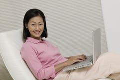 Mulher na cadeira usando o retrato do portátil imagens de stock royalty free