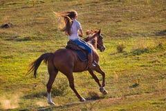 Mulher na calças de ganga que monta um cavalo Imagem de Stock Royalty Free