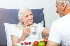 Mulher na cama com copo de café imagem de stock royalty free