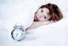 Mulher na cama com insônia que não pode dormir o fundo branco fotografia de stock royalty free