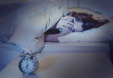 Mulher na cama com insônia que não pode dormir o fundo branco fotografia de stock
