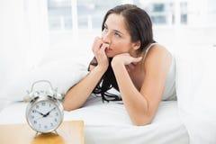 Mulher na cama com o despertador no primeiro plano Fotografia de Stock