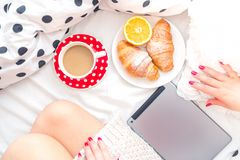 Mulher na cama com a tabuleta, o café da manhã e o café, relaxando num domingo de manhã Fotos de Stock