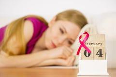 Mulher na cama, dia do câncer da mama do mundo no calendário Imagem de Stock