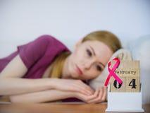 Mulher na cama, dia do câncer da mama do mundo no calendário Imagens de Stock