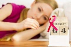 Mulher na cama, dia do câncer da mama do mundo no calendário Fotos de Stock Royalty Free