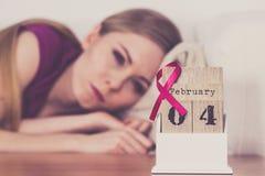 Mulher na cama, dia do câncer da mama do mundo no calendário Foto de Stock