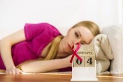 Mulher na cama, dia do câncer da mama do mundo no calendário Fotos de Stock