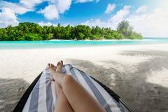 Mulher na cama do sol sob a palmeira na ilha tropical Imagens de Stock