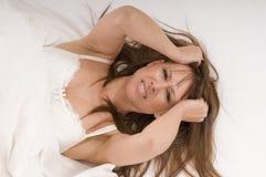 A mulher na cama sofre de uma dor de cabeça Imagem de Stock