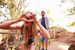 Mulher na caminhada com o homem que faz a forma do coração na câmera fotos de stock