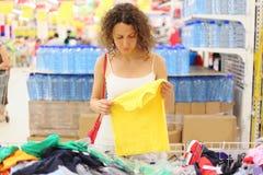 Mulher na camisa da terra arrendada da loja e vista nela foto de stock royalty free
