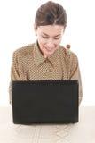 Mulher na camisa que senta e que usa o portátil para o bate-papo em linha Foto de Stock Royalty Free
