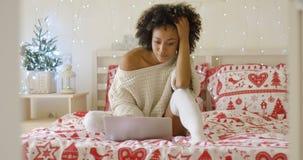 Mulher na camiseta na cama usando o laptop foto de stock royalty free