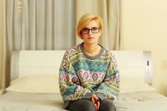 Mulher na camiseta colorida que senta-se na cama Fotografia de Stock Royalty Free