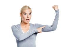 Mulher que toca em seus músculos na mão imagem de stock