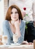 A mulher na casa de café e o homem com aumentaram atrás dela Imagens de Stock Royalty Free