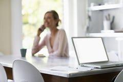 Mulher na chamada com portátil e originais na tabela Fotografia de Stock Royalty Free