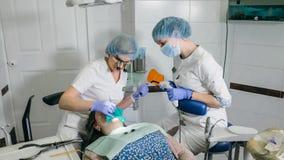A mulher na clínica do dentista consegue o tratamento dental encher uma cavidade em um dente Restauração dental e material compos foto de stock royalty free