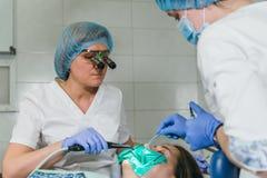 A mulher na clínica do dentista consegue o tratamento dental encher uma cavidade em um dente Restauração dental e material compos fotos de stock royalty free