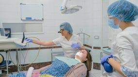 A mulher na clínica do dentista consegue o tratamento dental encher uma cavidade em um dente Restauração dental e material compos fotografia de stock royalty free