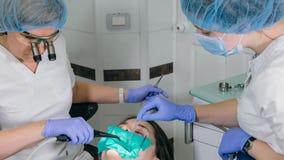 A mulher na clínica do dentista consegue o tratamento dental encher uma cavidade em um dente Restauração dental e material compos imagens de stock royalty free
