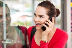 Mulher na compra da janela do telefone imagens de stock