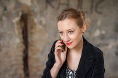 Mulher na construção velha que fala no telefone Fotografia de Stock