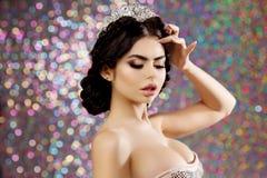 A mulher na coroa do vestido do lux, princesa da rainha ilumina o fundo do partido Foto de Stock