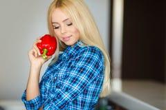 Mulher na cozinha com pimenta vermelha à disposição Foto de Stock Royalty Free