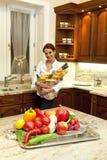 Mulher na cozinha com saco de compras Fotografia de Stock