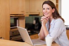 Mulher na cozinha com seu portátil fotos de stock