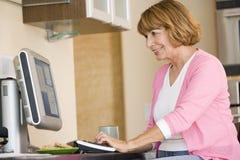 Mulher na cozinha com sorriso do computador e do café foto de stock royalty free