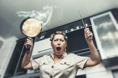 Mulher na cozinha com uma frigideira com uma panqueca e um a quentes Fotos de Stock Royalty Free