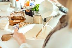 A mulher na cozinha derrama o leite medido em uma bacia imagens de stock