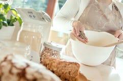 A mulher na cozinha derrama sementes de girassol em uma bacia com brea imagens de stock royalty free