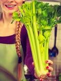 A mulher na cozinha guarda o aipo verde Imagem de Stock