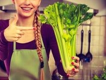 A mulher na cozinha guarda o aipo verde Fotos de Stock Royalty Free