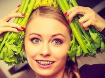 A mulher na cozinha guarda o aipo verde Foto de Stock Royalty Free