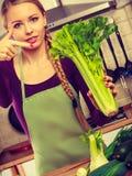 A mulher na cozinha guarda o aipo verde Fotografia de Stock