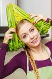 A mulher na cozinha guarda o aipo verde Imagens de Stock