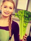 A mulher na cozinha guarda o aipo verde Fotos de Stock